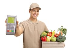 Delivery man with a payment terminal and a crate filled with gro. Ceries isolated on white background Royalty Free Stock Image