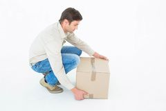 Delivery man picking cardboard box Royalty Free Stock Photos