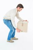 Delivery man picking cardboard box Stock Images