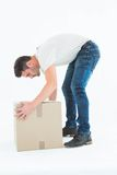 Delivery man picking cardboard box Stock Photos