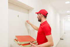 Delivery man with pizza boxes knocking on door Stock Photography