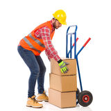 Delivery man place package on delivery cart Stock Images