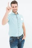 Delivery man pointing upward on white background Royalty Free Stock Image