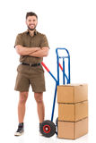 Delivery man posing with a luggage cart Royalty Free Stock Photo