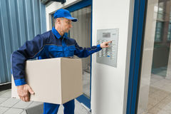 Delivery Man Pressing Button Of Intercom To Enter Building Royalty Free Stock Images