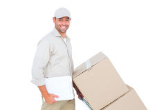 Delivery man pushing trolley of boxes on white background Stock Images