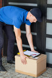 Delivery man putting down parcel Stock Photo