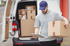 Delivery man reading notes on his clipboard. While holding package Royalty Free Stock Images