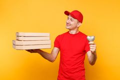 Delivery man in red cap t-shirt giving food order pizza boxes on yellow background. Male employee pizzaman royalty free stock photo