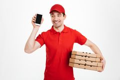 Delivery man in red t-shirt and cap holding stack of pizza boxes. And showing copyspace screen of cell phone meaning call or text  over white background Royalty Free Stock Photos