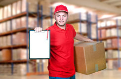 Delivery man in red uniform holding the box Royalty Free Stock Photos