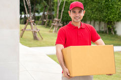 Delivery man in red uniform holding box stock photos