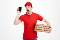 Delivery man in red uniform holding stack of pizza boxes and hol. Ding cell while having call isolated over white background Royalty Free Stock Photography