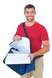 Delivery man removing pizza box from bag Stock Photos