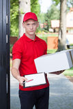 Delivery man requesting a signature Royalty Free Stock Photography