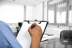 Delivery man's hand signing document on clipboard Stock Photography
