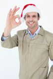 Delivery man in Santa hat gesturing OK sign Stock Photos