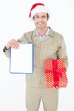 Delivery man in Santa hat holding clipboard and gift Royalty Free Stock Image