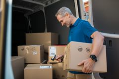 Deliveryman scanning parcel barcode. Delivery man scanning cardboard boxes with barcode scanner. Courier holding parcel and scanning barcode with barcode reader royalty free stock images