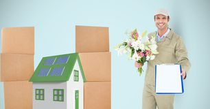 Delivery man showing clipboard while holding flowers by parcels and 3d house. Digital composite of Delivery man showing clipboard while holding flowers by Royalty Free Stock Photography