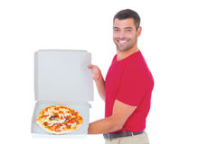 Delivery man showing fresh pizza on white background Royalty Free Stock Photography