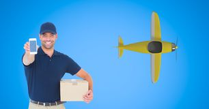 Delivery man showing smart phone with airplane flying in background. Digital composite of Delivery man showing smart phone with airplane flying in background stock photo