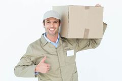 Delivery man showing thumbs up while carrying cardboard box Stock Photography