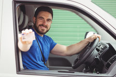 Delivery man sitting in his van. While showing his driving licence Stock Image