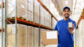 Delivery man with smartphone and box at warehouse. Mail service, technology and shipment concept - happy indian delivery man or warehouse worker with smartphone stock photography