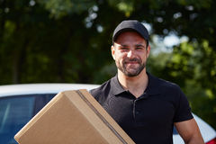Delivery man. Smiling delivery man holding a paper box royalty free stock images