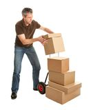Delivery man staking packages on hand truck. Isolated on white Royalty Free Stock Image