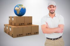 Composite image of delivery man standing arms crossed. Delivery man standing arms crossed against grey background Stock Photos