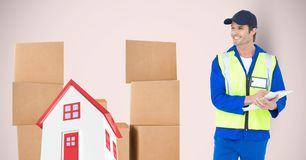 Delivery man standing by 2d house and parcels. Digital composite of Delivery man standing by 2d house and parcels Stock Photos