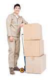 Delivery man standing beside luggage trolley with cardboard boxes Stock Image