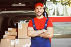 Delivery man standing. Near car stock photos