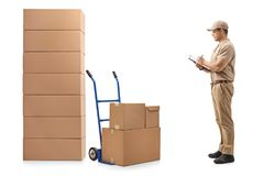 Delivery man standing next to a hand truck and a stack of boxes. Full length profile shot of a delivery man standing next to a hand truck and a stack of boxes Royalty Free Stock Images
