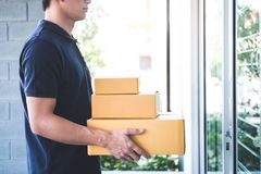 Delivery man standing with parcels in hands outdoors waiting homeowner open door, Home delivery service and working with service royalty free stock images
