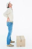 Delivery man suffering from back pain standing by box Stock Image