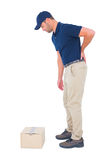Delivery man suffering from backache on white background. Full length side view of delivery man suffering from backache on white background Royalty Free Stock Photography