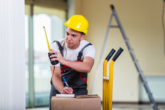 The delivery man taking dimensions with tape measure Stock Photo