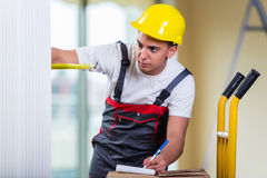 The delivery man taking dimensions with tape measure Royalty Free Stock Images
