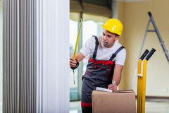 The delivery man taking dimensions with tape measure Stock Photos