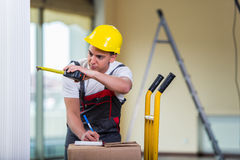 The delivery man taking dimensions with tape measure Royalty Free Stock Photo