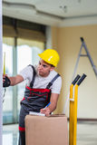 The delivery man taking dimensions with tape measure Royalty Free Stock Photography
