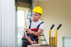 The delivery man taking dimensions with tape measure Royalty Free Stock Photos