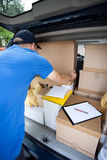 Delivery man taking out package Stock Images