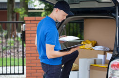 Delivery man taking package from car Royalty Free Stock Photography