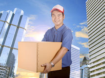 Delivery man toothy smiling face and holding card box delivering Royalty Free Stock Photos