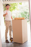 Delivery man with trolley of boxes giving thumbs up. Outside the warehouse Stock Photography