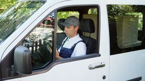 Delivery man typing on digital tablet without leaving the van. Delivery man in uniform checking packages while sitting in car and typing on digital tablet stock video footage